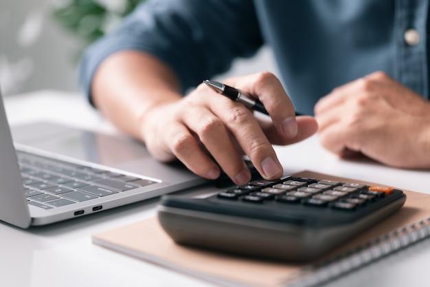 Uomo che usa la calcolatrice che conta le tasse sulle finanze concetto di contabilità di analisi aziendale