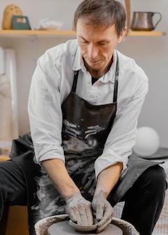 Uomo che utilizza l'argilla per il colpo medio di ceramiche