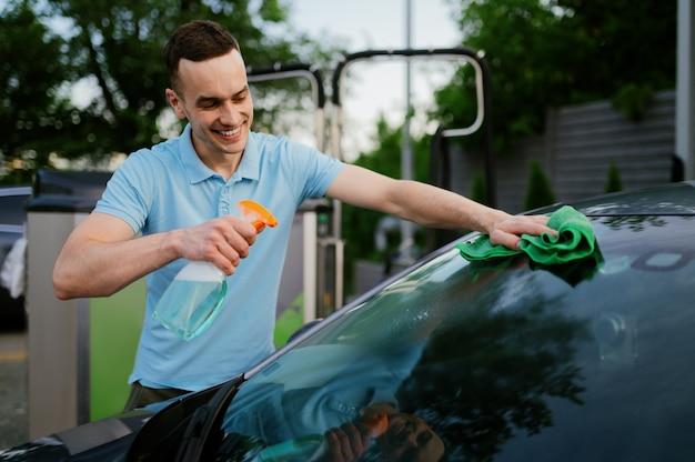 Uomo che usa un detergente e uno straccio, stazione di lavaggio automatico a mano. industria o attività dell'autolavaggio. la persona di sesso maschile pulisce il suo veicolo dallo sporco all'aperto