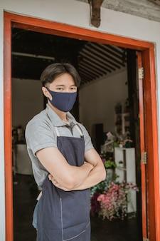 Uomo che utilizza la maschera per il viso fiorista in piedi braccio incrociato nel negozio di fiori della porta d'ingresso con fiori freschi all'interno del suo negozio di fiori