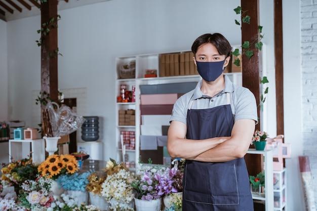 Uomo che utilizza maschera facciale fiorista in piedi braccio incrociato con fiori freschi nel suo negozio di fiori seguendo il protocollo sano