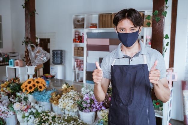 L'uomo che utilizza la maschera per il viso fiorista in piedi dà il pollice con fiori freschi nel suo negozio di fiori seguendo il protocollo sano