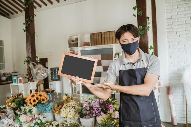 Uomo che utilizza la maschera per il viso fiorista in piedi tenendo piccola lavagna vuota fiori freschi nel suo negozio di fiori seguendo il protocollo sano