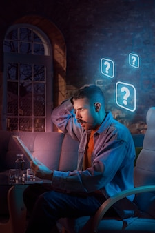 Uomo che usa gadget e riceve notifiche al neon a casa di notte. seduti in poltrona, navigando in internet e cercando informazioni. abuso dei social media, chat e navigazione, dipendenza da gadget.