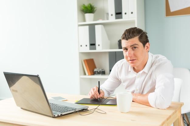 Uomo che utilizza tavoletta grafica in ufficio e ti guarda