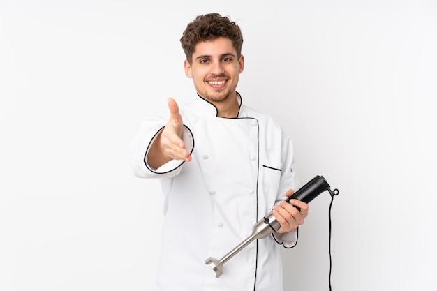 Uomo che usando il frullatore a immersione sulla stretta di mano bianca della parete dopo il buon affare