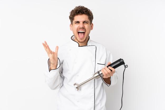 Uomo che usando il frullatore a immersione sulla parete bianca infelice e frustrato con qualcosa