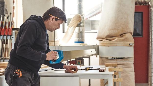 Uomo che usa una sega a mano per tagliare il legno
