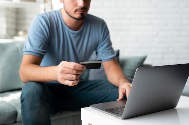 Uomo che usa la sua carta di credito per giocare online per un ordine