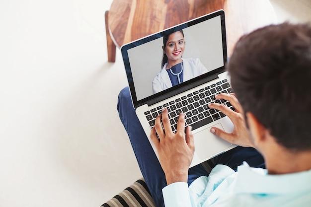 Uomo che utilizza il suo laptop per ottenere un consulto medico online dal medico indiano