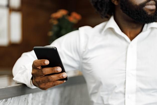 Uomo che utilizza il suo smartphone vicino alla reception in hotel