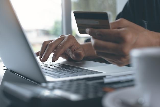 Uomo che utilizza computer portatile e carta di credito per l'online banking