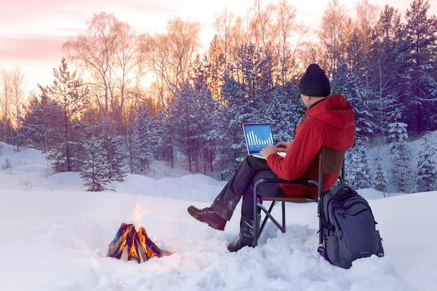 Uomo che utilizza computer portatile sulla sedia a sdraio vicino al fuoco nella foresta invernale. lavoro a distanza.
