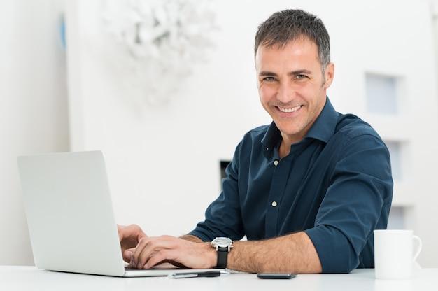 Uomo che per mezzo del computer portatile alla scrivania