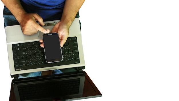 Uomo che utilizza laptop e mano touch screen smart phone.