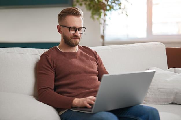 Uomo che usa il laptop in soggiorno