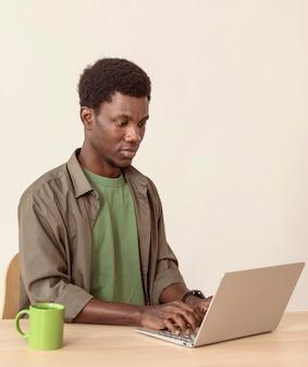 Uomo che utilizza laptop e seduto al suo spazio di lavoro
