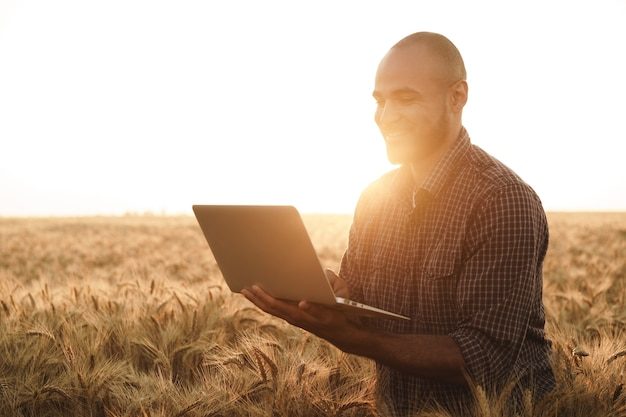 Uomo che usa il laptop mentre si trova in un campo di grano al tramonto