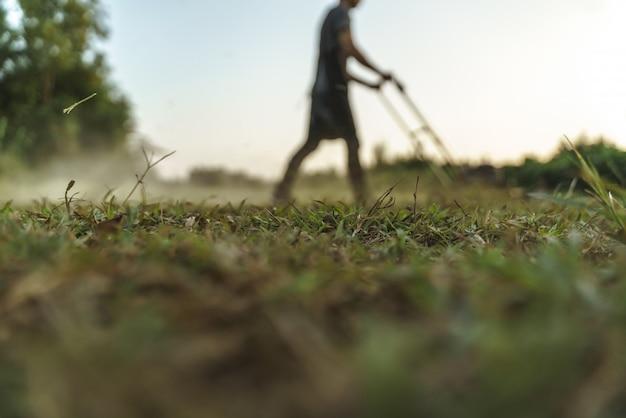 Uomo che usando l'erba di taglio della falciatrice da giardino