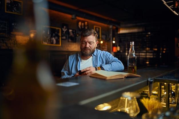 Uomo che utilizza il telefono cellulare al bancone del bar. una persona di sesso maschile che riposa in un pub, emozioni umane, attività di svago, vita notturna