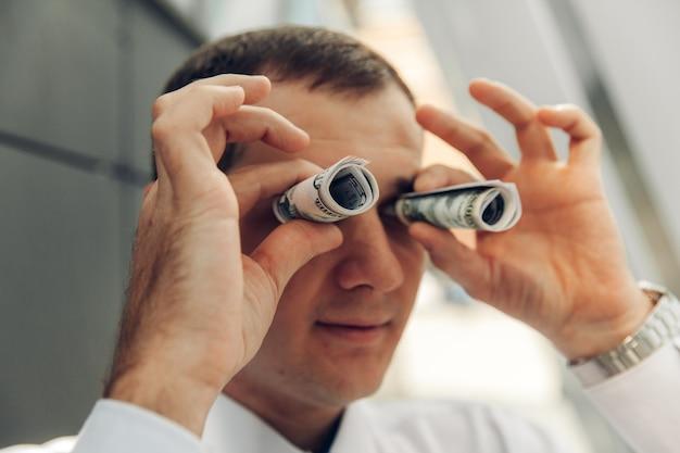 Uomo che usa soldi come un binocolo. l'uomo ha attorcigliato il denaro con una cannuccia vicino agli occhi.