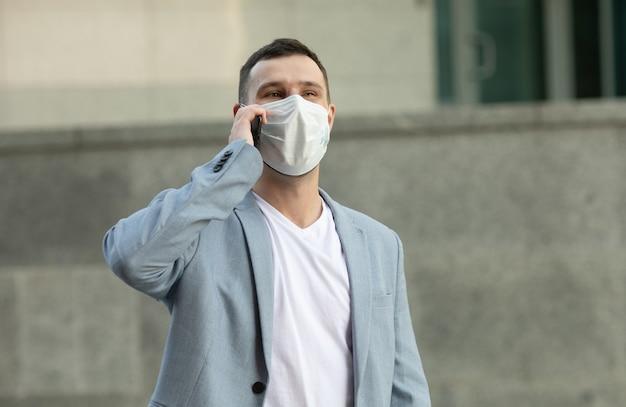 Uomo che utilizza il telefono in maschera per la strada