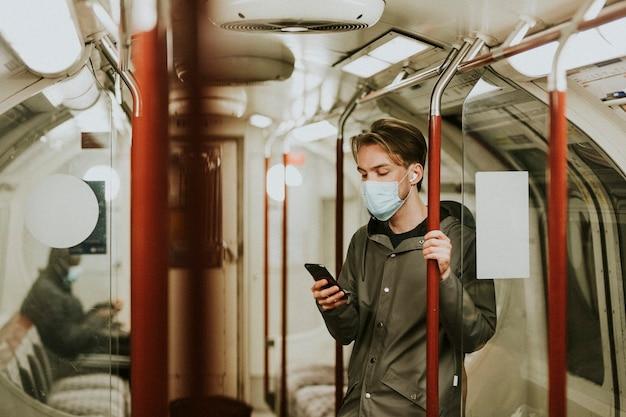 Uomo che usa un telefono su un treno nella nuova normalità