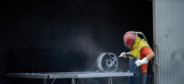 Uomo che usa la sabbiatrice per pulire i dettagli metallici al lavoro