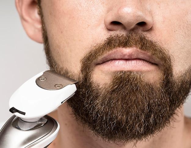 Uomo che utilizza un primo piano della macchina da barba
