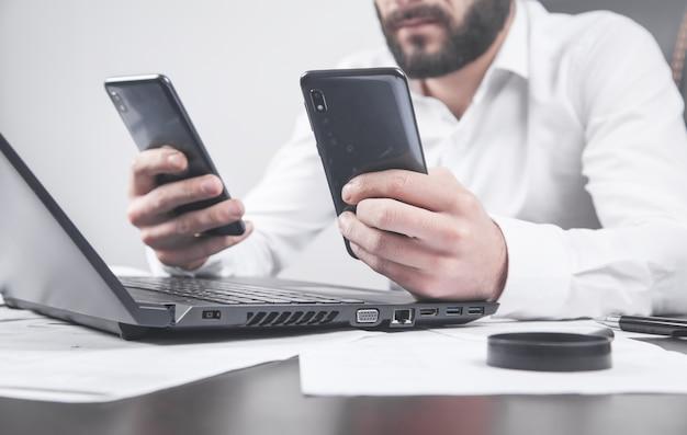 Uomo che utilizza smartphone. scrivania da ufficio moderna. tecnologia