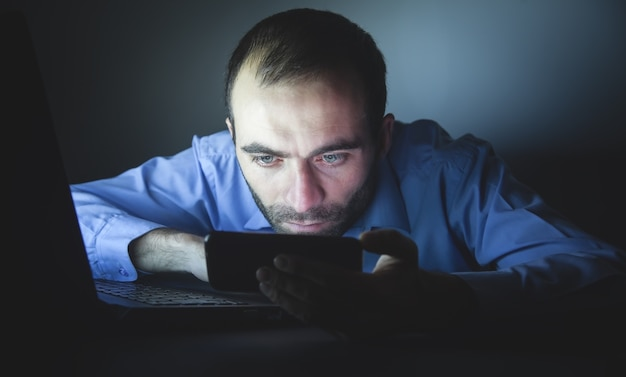 Uomo che utilizza smartphone di notte. tecnologia. attività commerciale