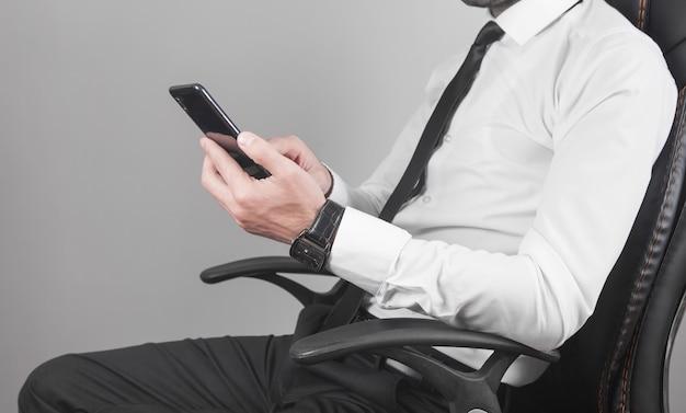 Uomo che utilizza smartphone in ufficio.