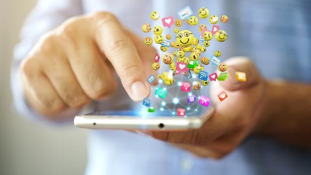 Uomo che utilizza lo smartphone che invia le icone dell'emoticon dei messaggi di testo. concetto di rete sociale, rendering 3d