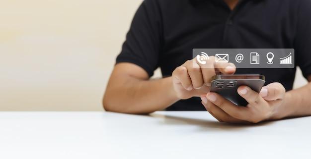 Uomo che utilizza smartphone con icone di contatto e lavoro. connessione di informazioni sulla tecnologia online dell'applicazione sul telefono cellulare.