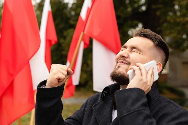 Uomo che per mezzo dello smartphone con le bandiere della polonia dietro