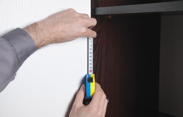 Uomo che utilizza il metro a nastro durante l'installazione di nuovi mobili in casa.