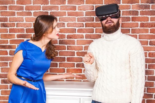 L'uomo che usa l'auricolare vr e sua moglie è arrabbiato