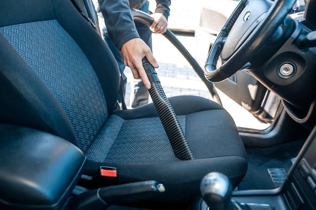 Uomo che aspira, aspirapolvere interni di un'auto con un aspirapolvere, concetto di pulizia