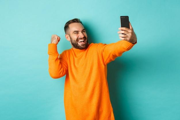 Uomo che chiama video, sembra felice e si rallegra di buone notizie, facendo pompare il pugno