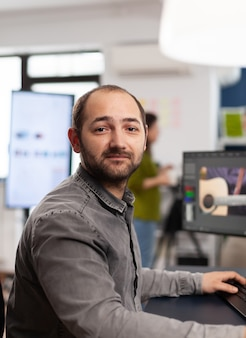 Editor video uomo che guarda la telecamera, lavora con filmati e suoni su un computer con due display