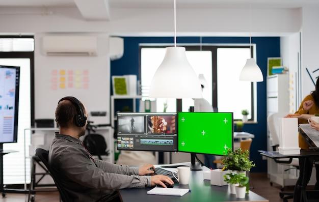 Videografo uomo con auricolare che modifica film in software di post produzione che lavora a schermo verde, display chroma key isolato del computer