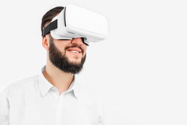 Un uomo con gli occhiali virtuali, primo piano, su un muro bianco