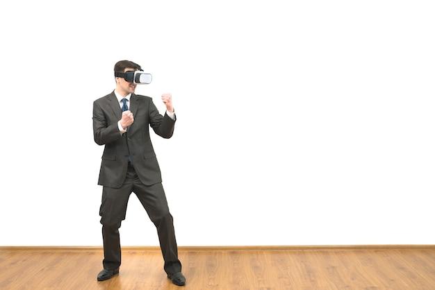 L'uomo con gli occhiali per realtà virtuale che combatte su uno sfondo di muro bianco