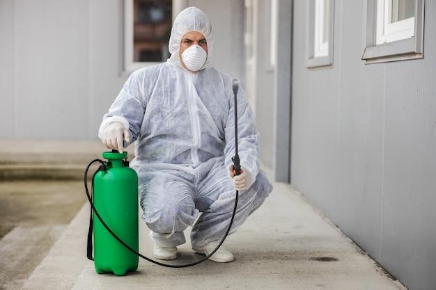 Uomo in tuta protettiva contro i virus e maschera che disinfetta gli edifici del coronavirus con lo spruzzatore. epidemia.
