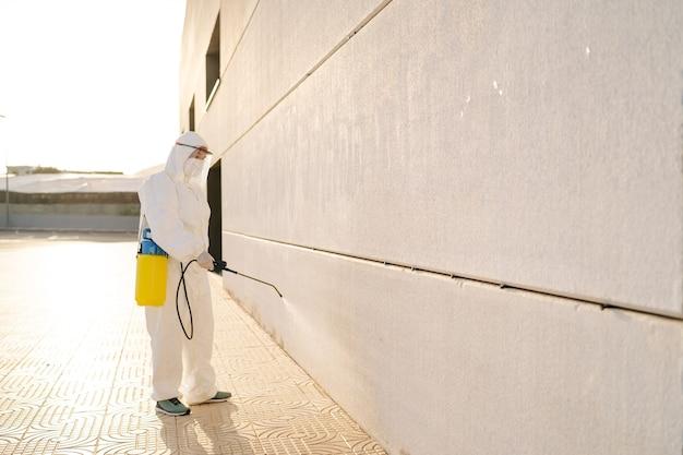 Uomo in tuta protettiva contro i virus e maschera che disinfetta gli edifici del coronavirus con lo spruzzatore. prevenzione delle infezioni e controllo dell'epidemia. pandemia mondiale.