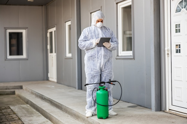 Uomo in tuta protettiva contro i virus e maschera che guarda e digita sul tablet, disinfettando gli edifici del coronavirus con lo spruzzatore.