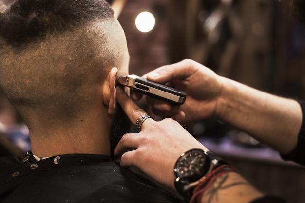 Uomo in visita dal parrucchiere nel negozio di barbiere