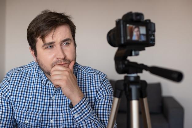 Man vlogger che registra video blog. vlogger che utilizza una videocamera montata su un treppiede per registrare video, coronavirus, malattia, infezione, quarantena, mascherina medica