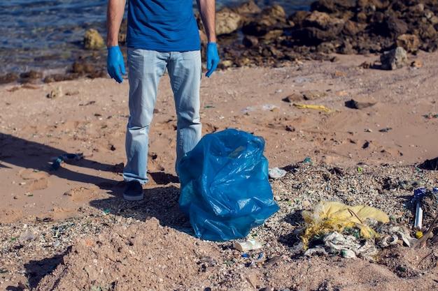 Uomo volontario con una grande borsa per la raccolta dei rifiuti sulla spiaggia. concetto di inquinamento ambientale