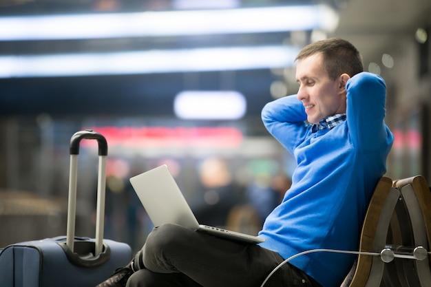 L'uomo in attesa accanto alla sua valigia